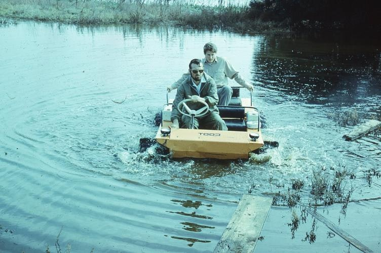Two people on a aquatic vehicle in the middle of a body of water