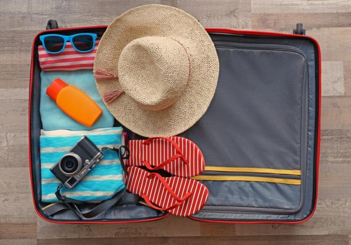 A view from above of an opened packed suitcase.  The suitcase contains a straw hat with wide brim, red and white stiped flip flops, a camera, an orange bottle like a sunscreen bottle, a pair of blue-framed sunglasses, and a few towels.