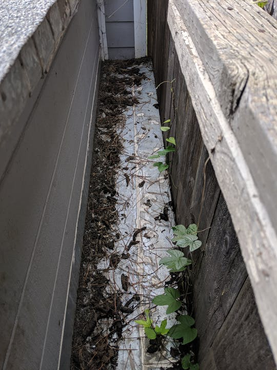A long recessed area surrounded on all sides by walls - some wooden and some metal. The bottom of the area is metal and is covered with raccoon feces.