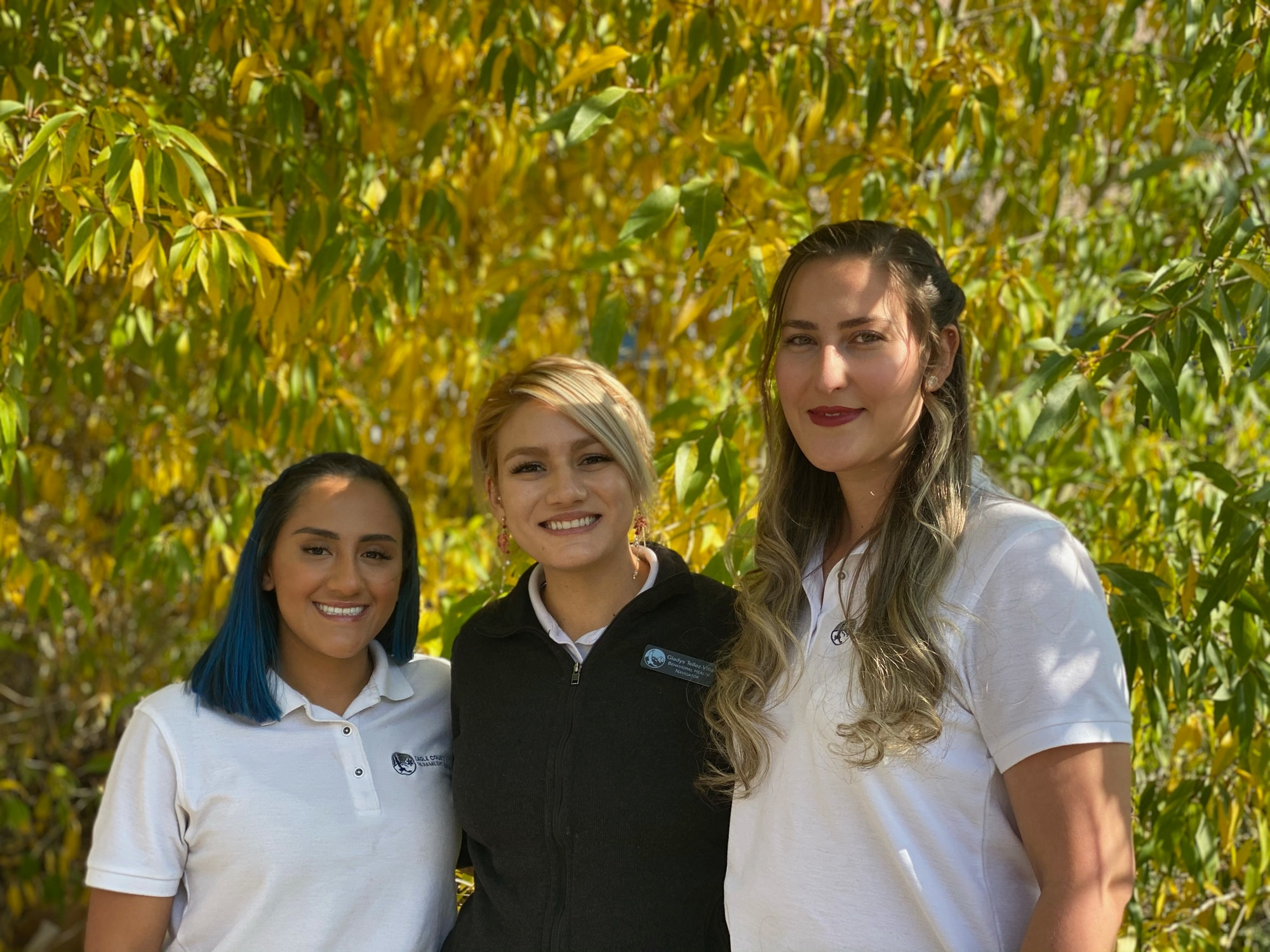 Photo of Coco Andrade, Gladys Tellez-Villa and Diana Bonilla in front of an autumn cottonwood tree.
