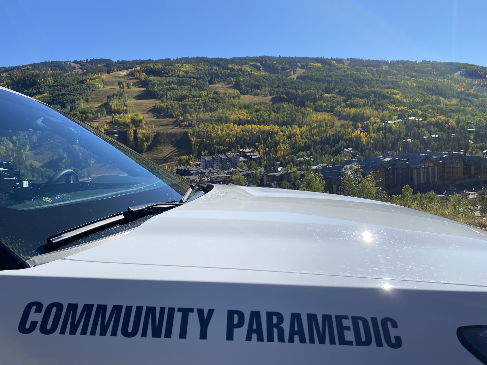 """Image of Community Paramedic SUV, close-up on the words """"Community Paramedic"""" with a mountain and yellow aspen leaves in the background."""