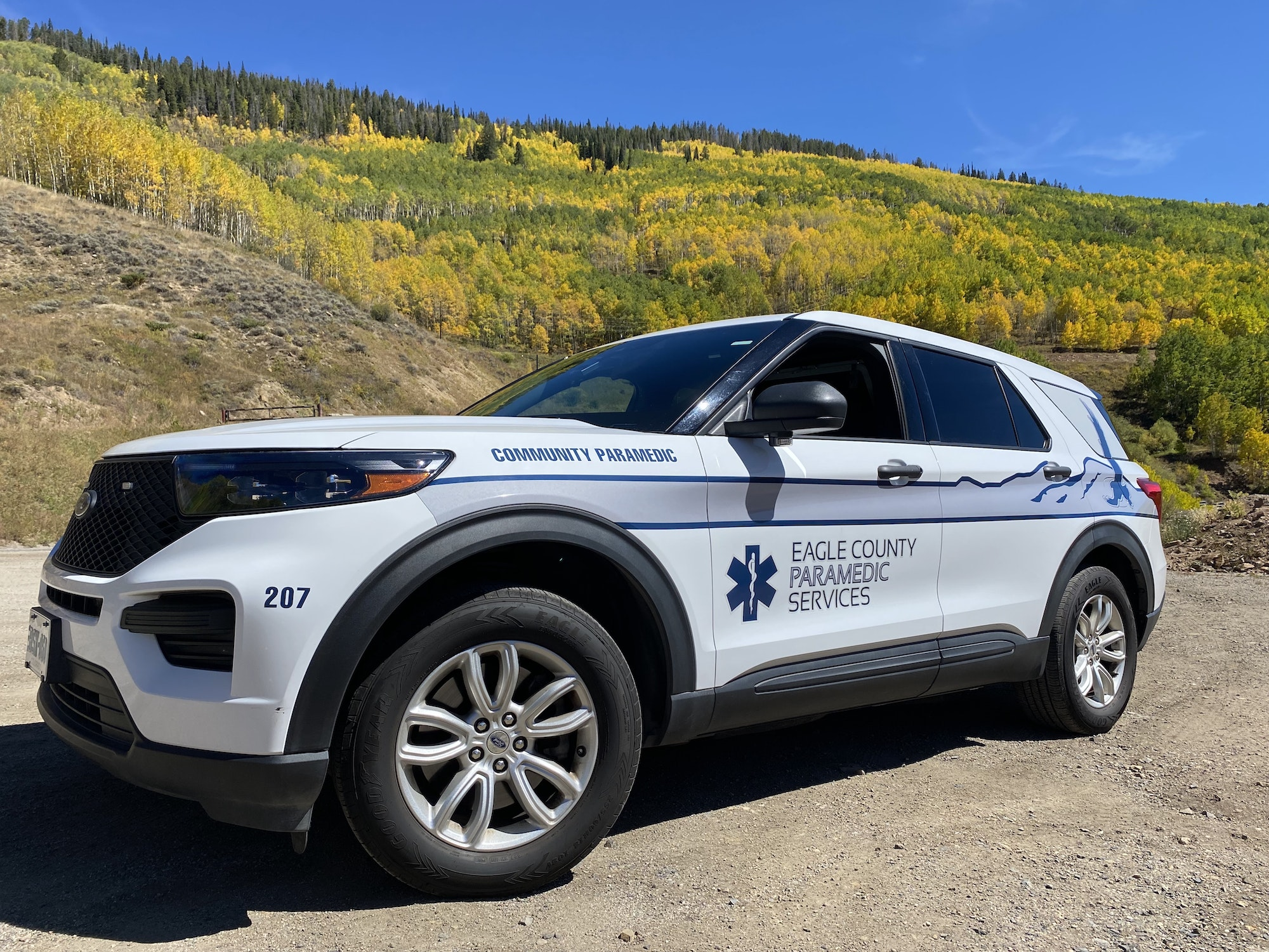 Community Paramedic SUV parked with changing yellow aspen leaves in the background.
