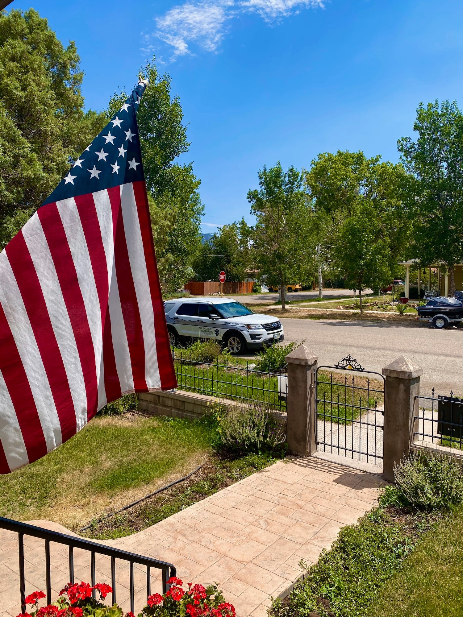 American flag on a house with a Community Paramedic vehicle parked by the curb