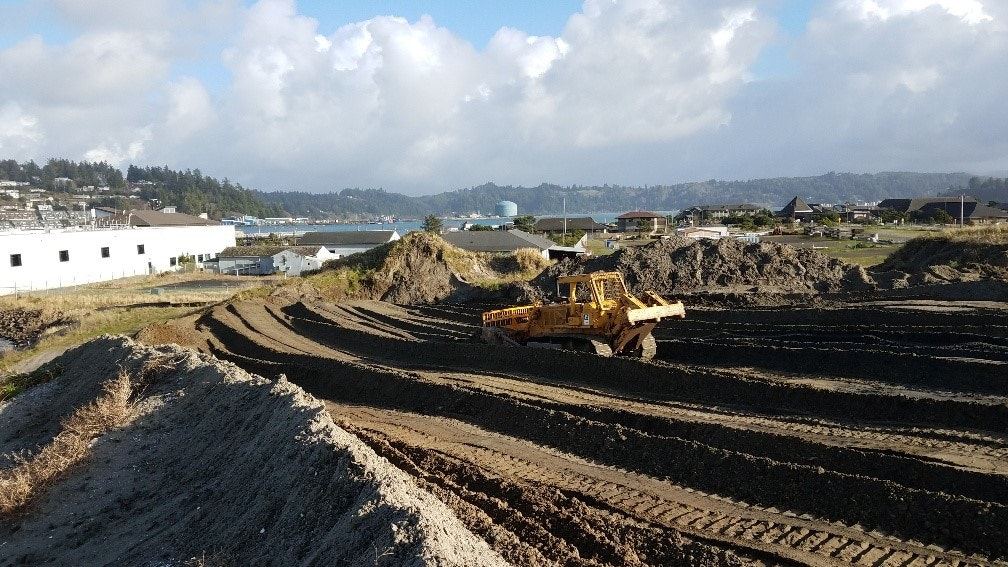 Digger moving dirt at the South Beach dredge material disposal site