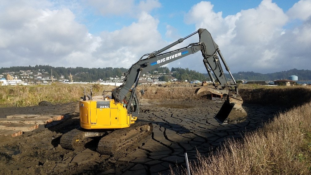 Excavator moving dirt at the South Beach dredge disposal site