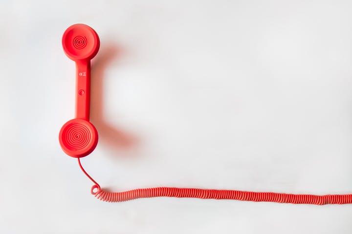 A portrait photo of a red landline phone