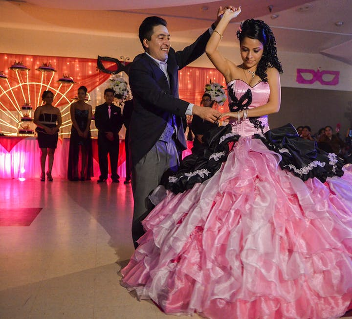 Couple dancing. Girl has a big puffy pink dress on. Girl is being twirled