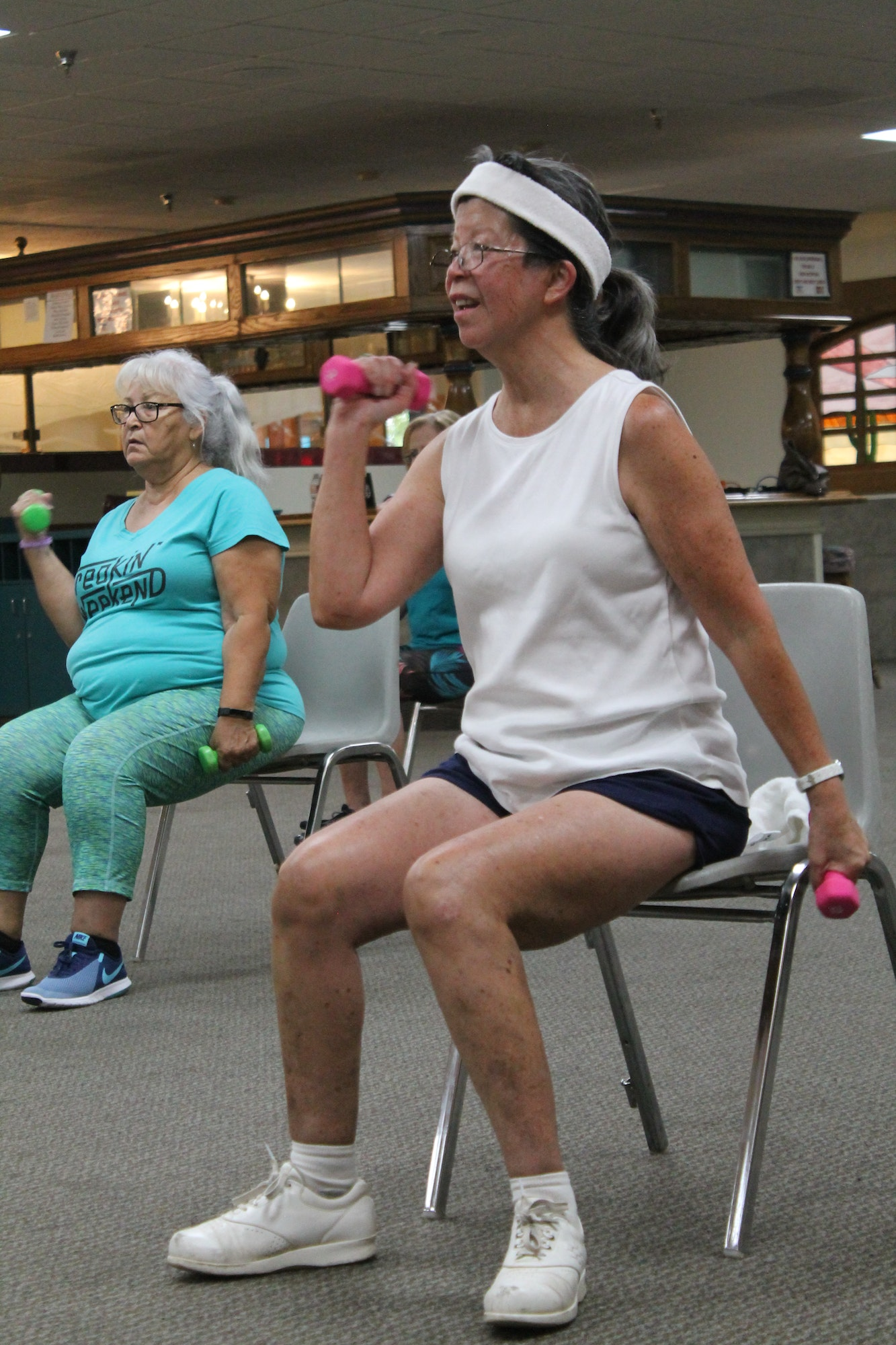 Two women enjoying the Fitness and Fun Exercise Class sitting on chairs with weights in each hand
