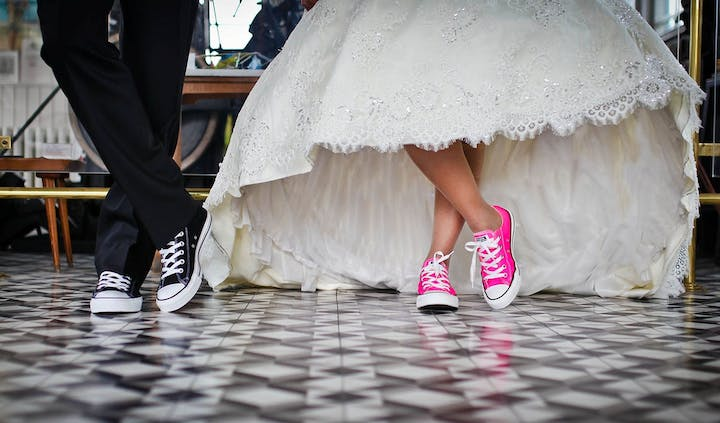 Couple wearing converse crossed legs at the ankles in wedding attire
