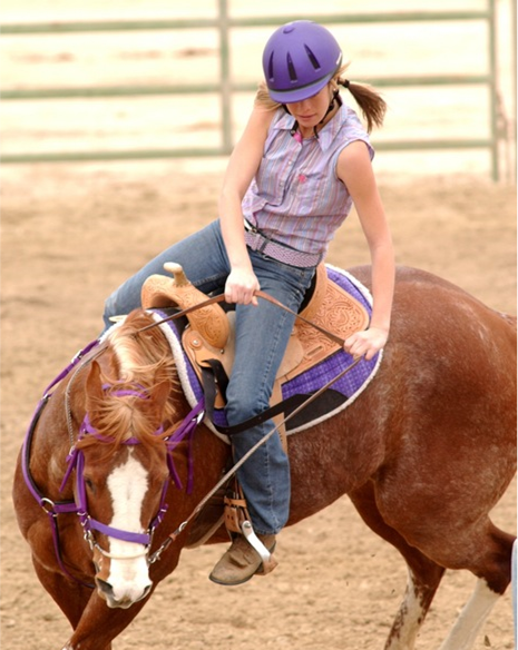 Girl riding horse at equestrian