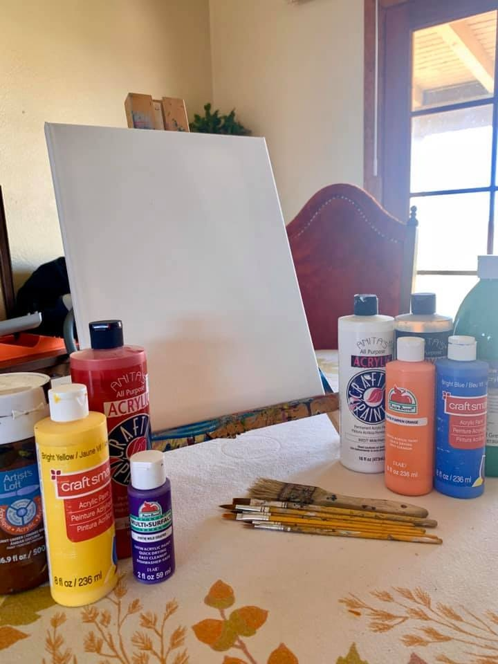 Different bottles of paint with paint brushes and a canvas. Supplies for the online painting class