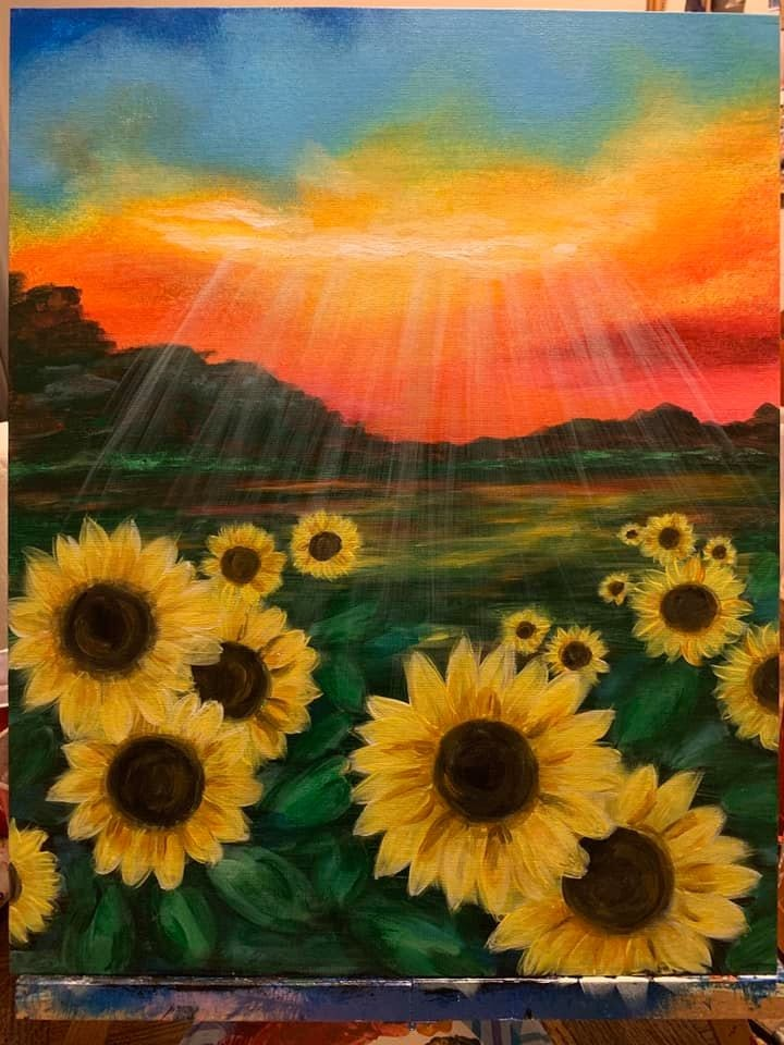 Blue clouds with a orangish red sunset over the mountains with streams of sunlight shining onto a field of sunflowers painted onto a canvas