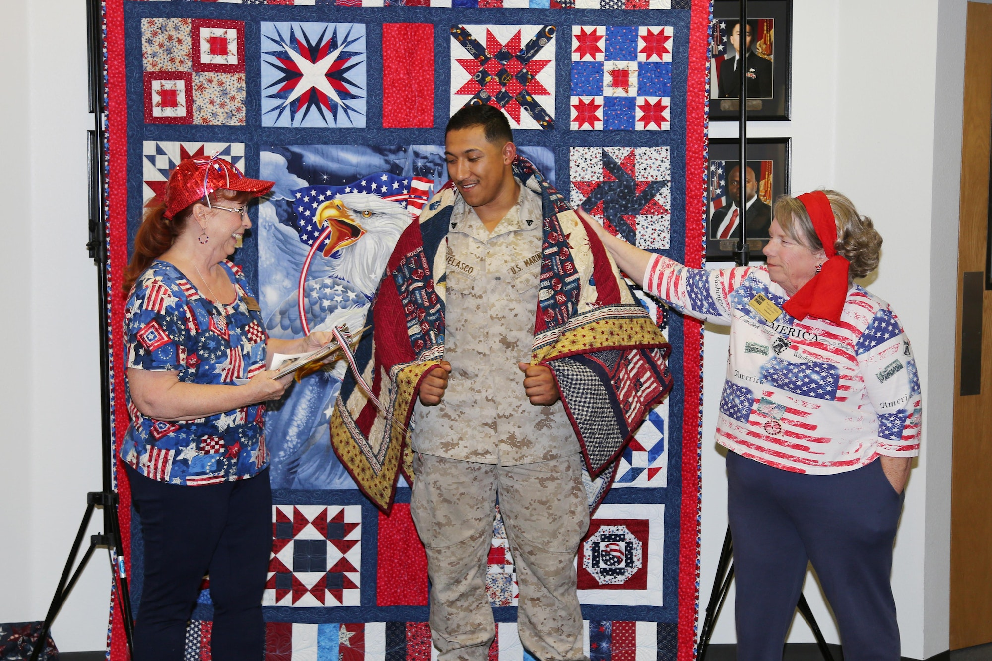 Two women beside soldier who has just received a quilt of valor quilt