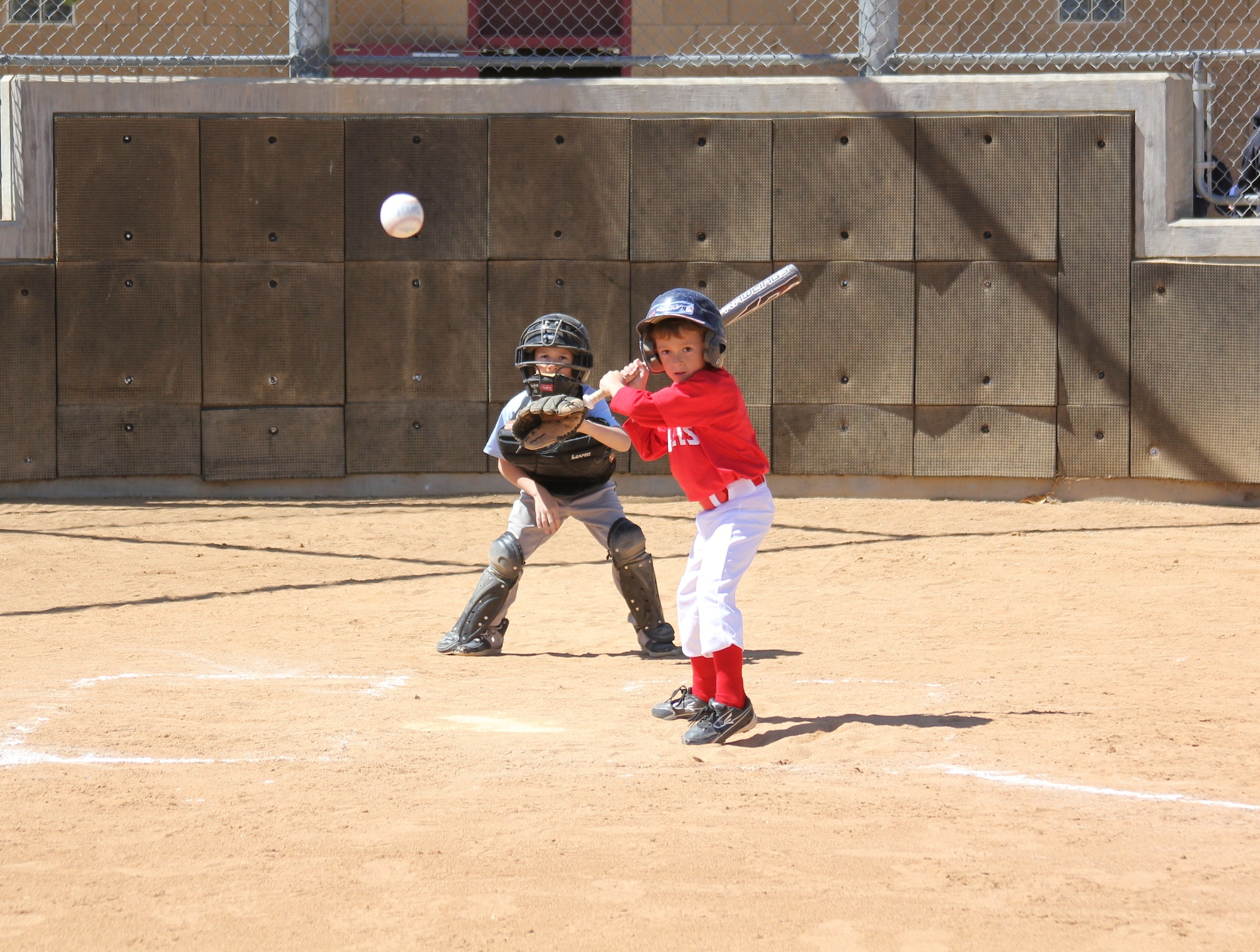 Little boy up to bat ready to swing with catcher behind him