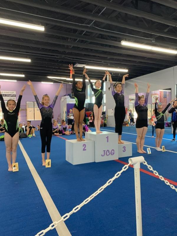 Girls posing with arms up in order from 1st place to 7th place for gymnastics