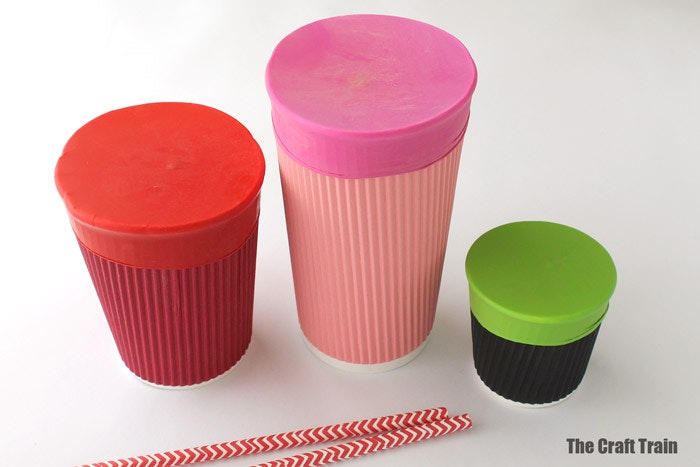 3 different sized paper cups with balloons stretched over top of all three to create paper cup drums. With paper straws next to them for drum sticks