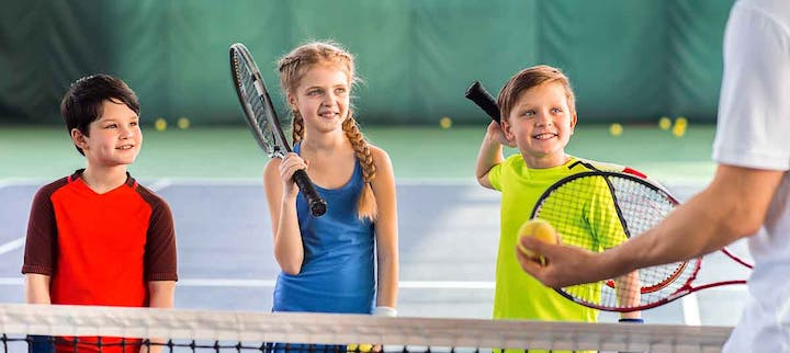 3 kids with tennis rackets smiling waiting to learn how to play tennis