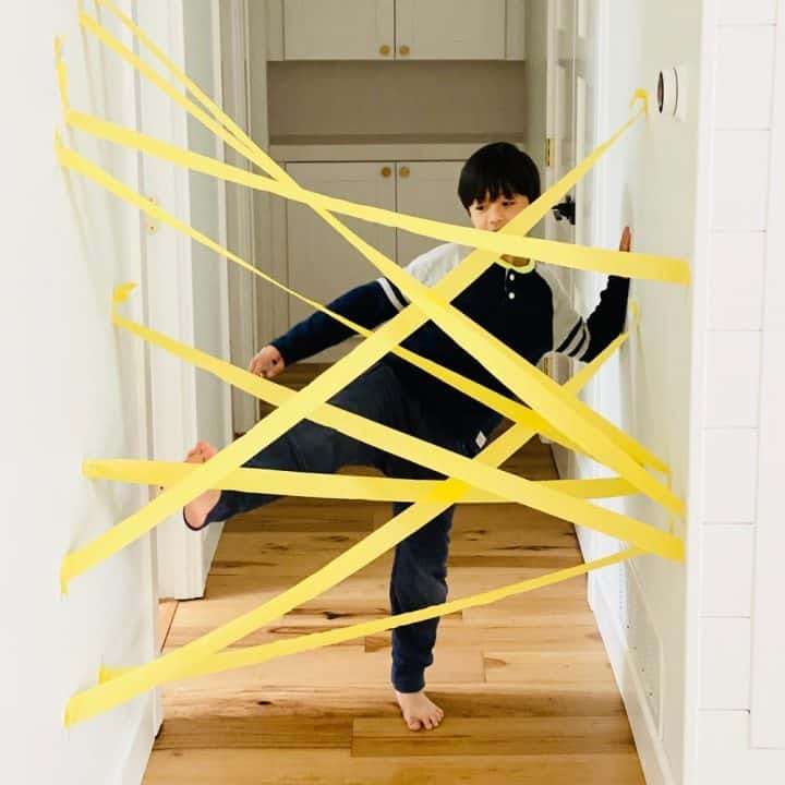 Young boy with leg up to try and get through the paper streamer obstacle course set in front of him in the hallway