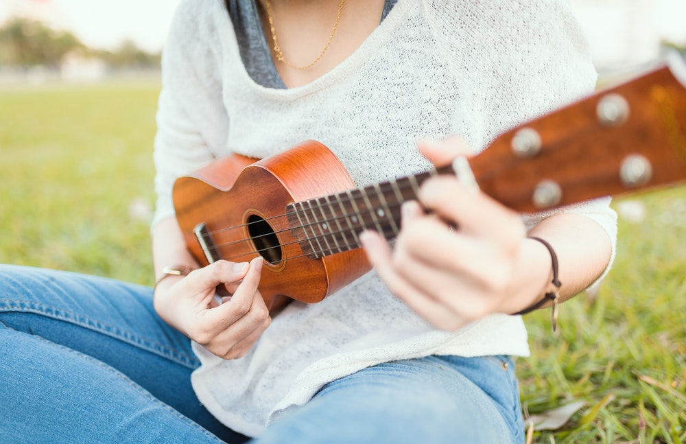 Person playing ukulele. View of person playing up close.
