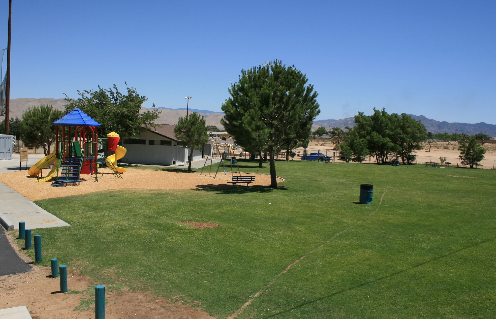 May contain: grass, plant, furniture, bench, playground, and play area
