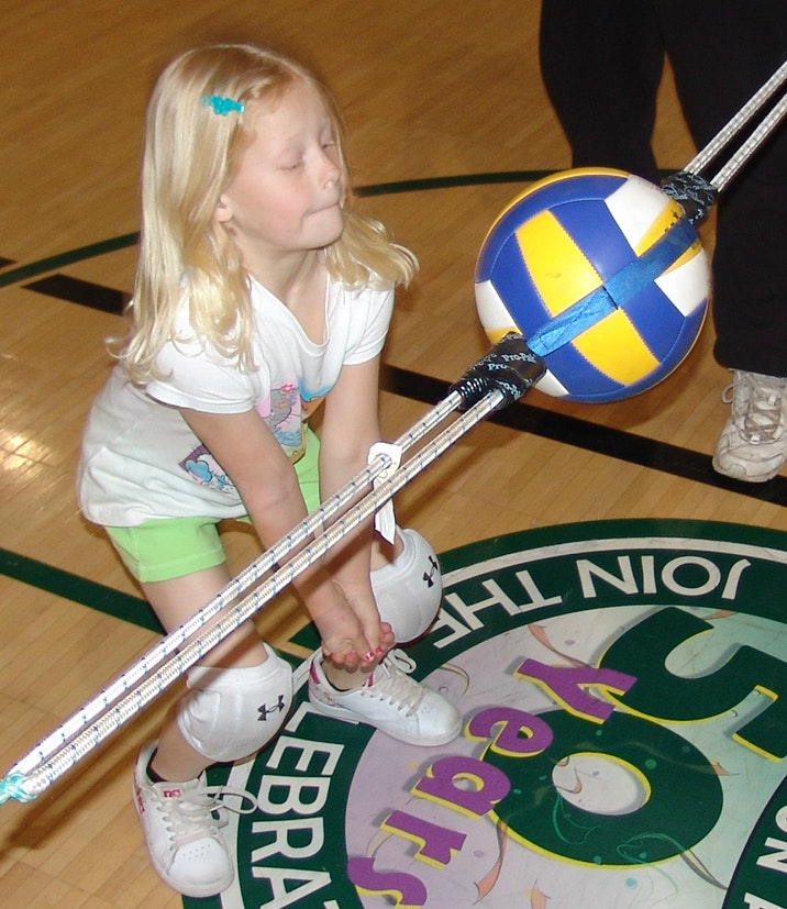 Young girl learning how to hit a volleyball