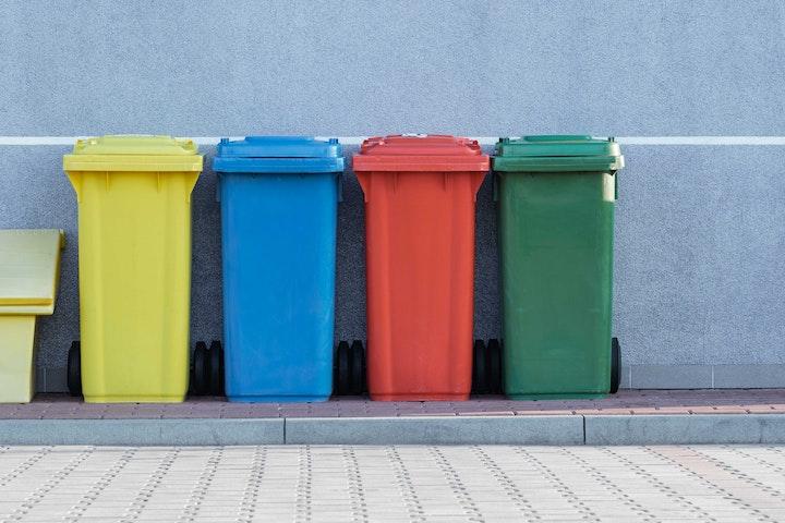 Row of colorful trashcans on sidewalk