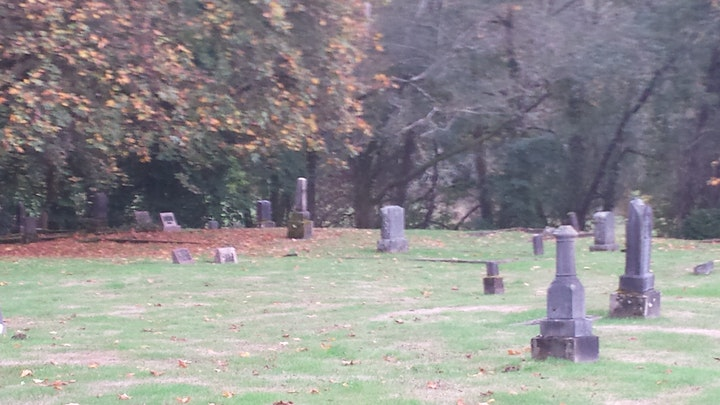 Photo of an old section of Maplewood cemetery in October with leaves in their autumn colers