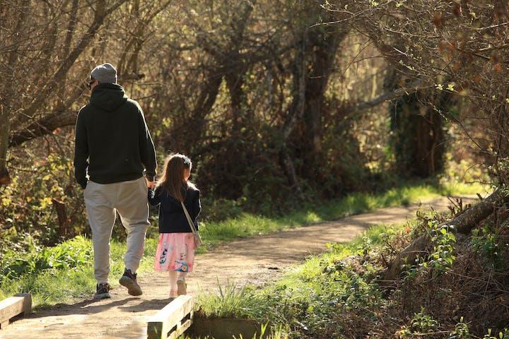 Man, child walking on a trail