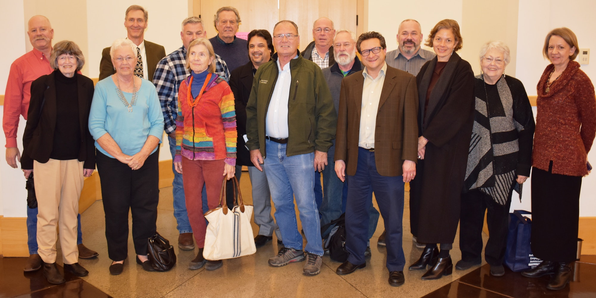 Members of the Measure  X committee members standing together in a group photo in the lobby of the Marina Branch Library