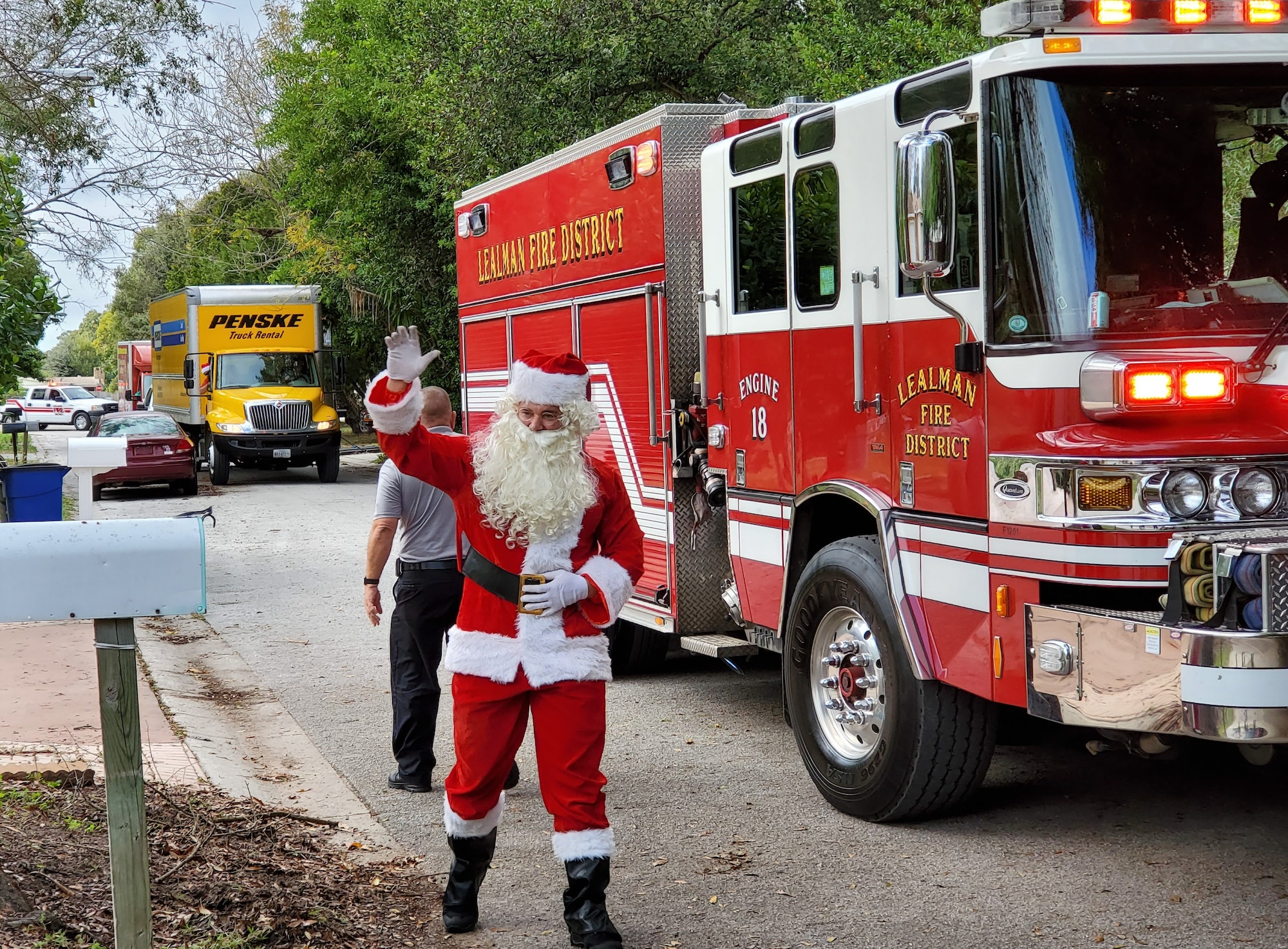 Picture of Santa waving next to a fire truck