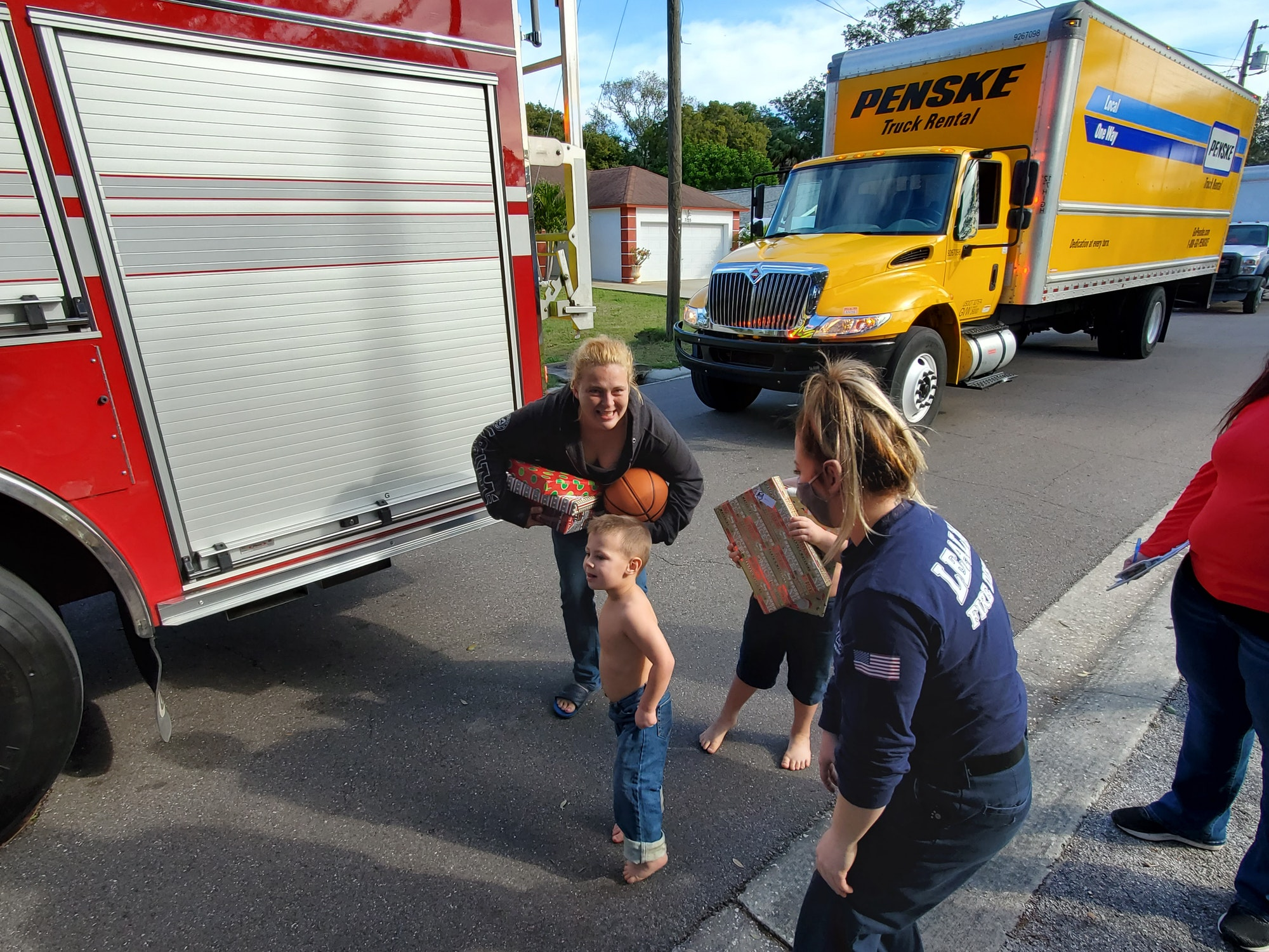 Trucks, firefighter, woman, and two little boys