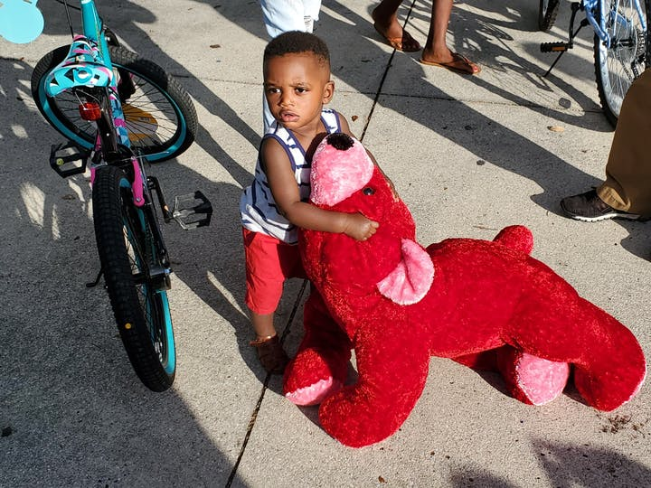 Little boy holding a stuffed animal next to a bike 12/24/2020