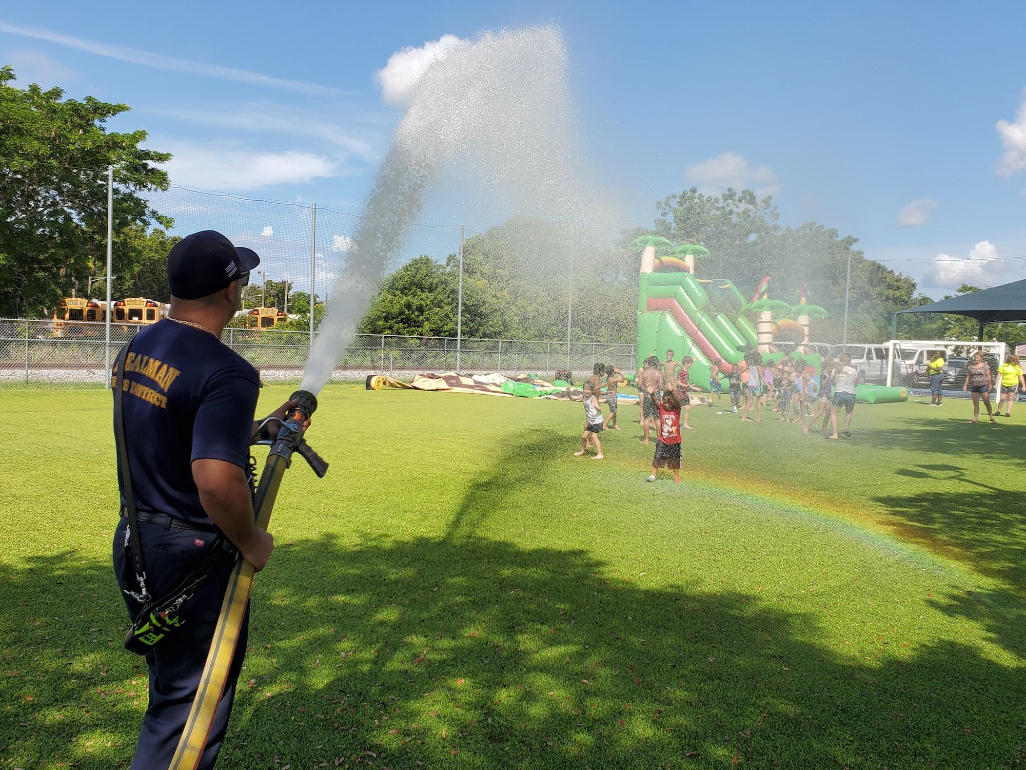 Firefighter spraying water on children