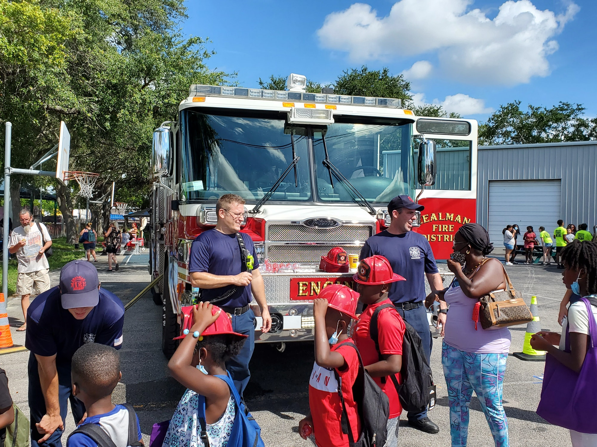 Firefighters talking with kids in front of a fire truck 08/07/2021