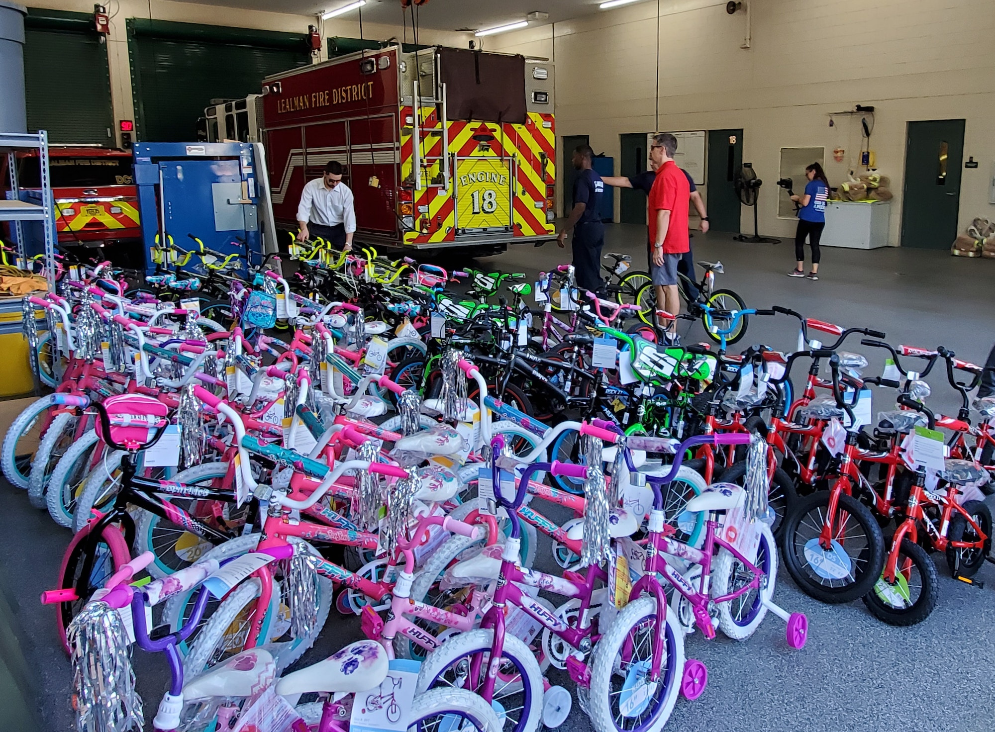 Picture of Bikes inside Fire Station 18 with people, and fire engine