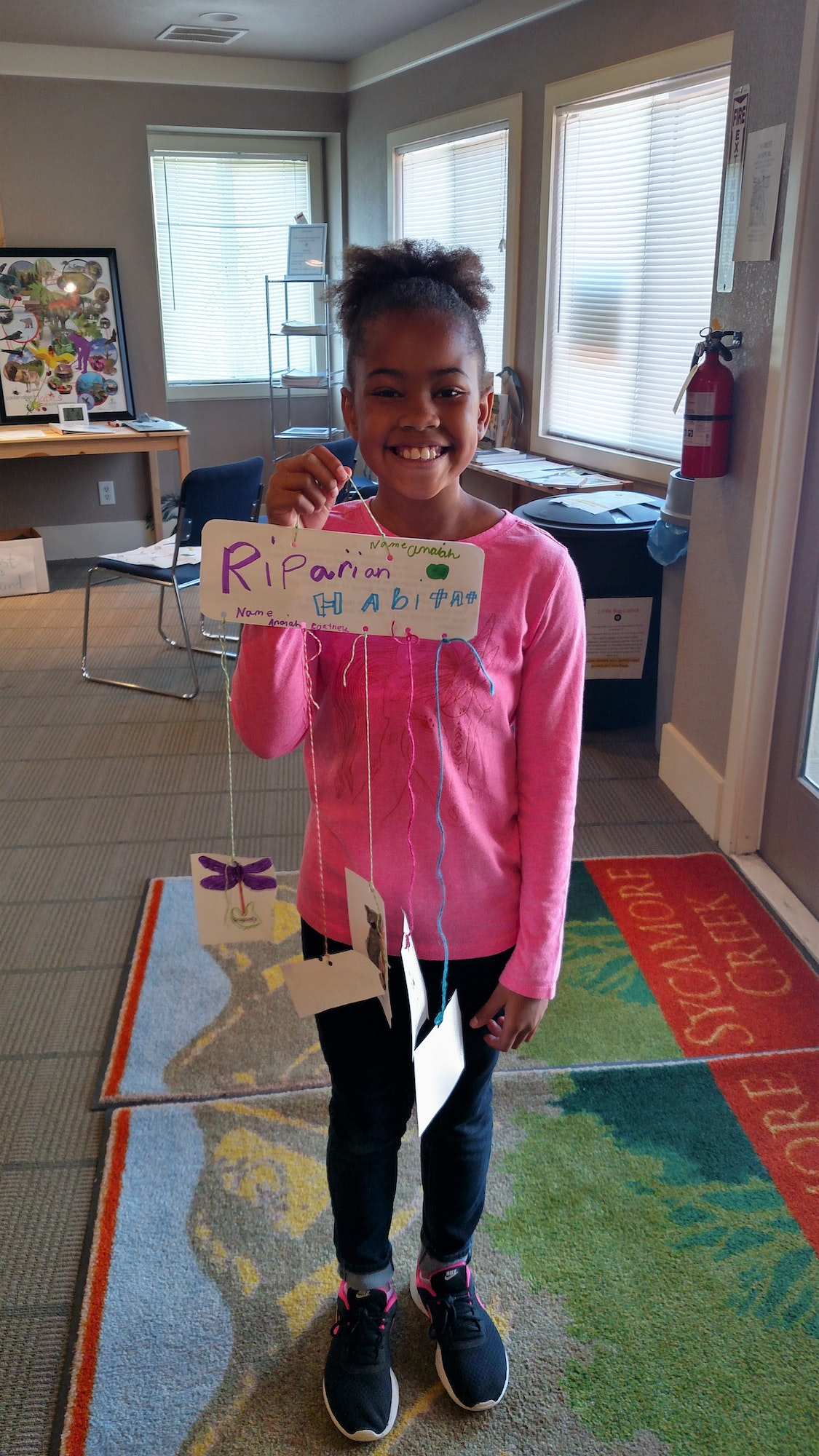 Homeschool student showing her riparian habitat craft