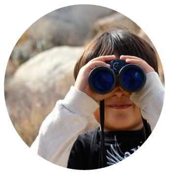 photo of a little boy looking through binoculars