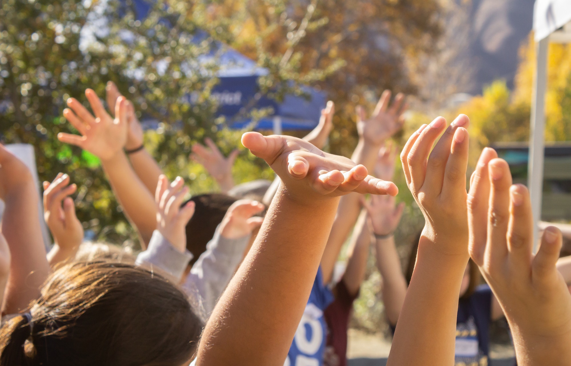Image of students outside with their hands in the air.