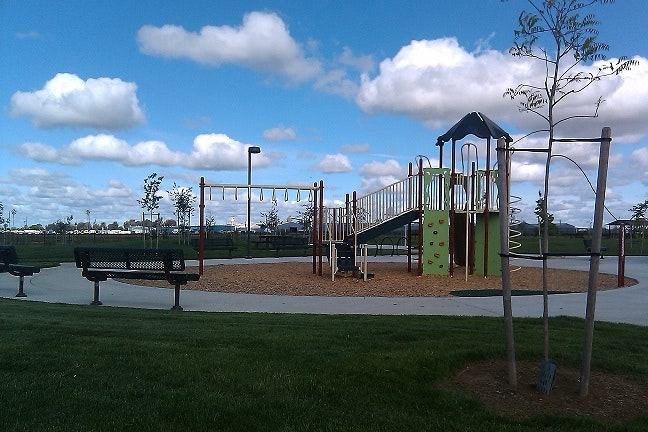 May contain: furniture, bench, plant, grass, playground, play area, park, lawn, and outdoors