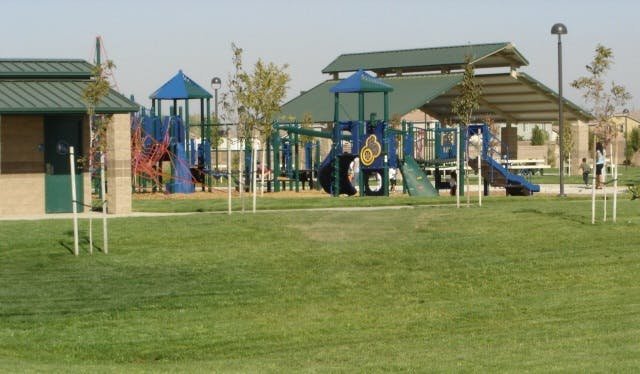 Daytime view of park playground and shade structure.
