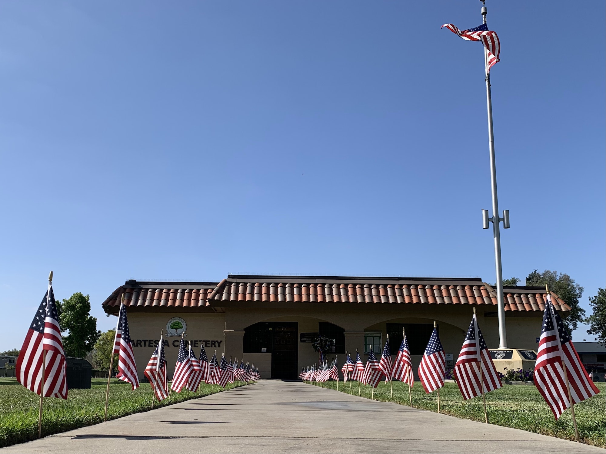 Front picture of cemetery office building with flags