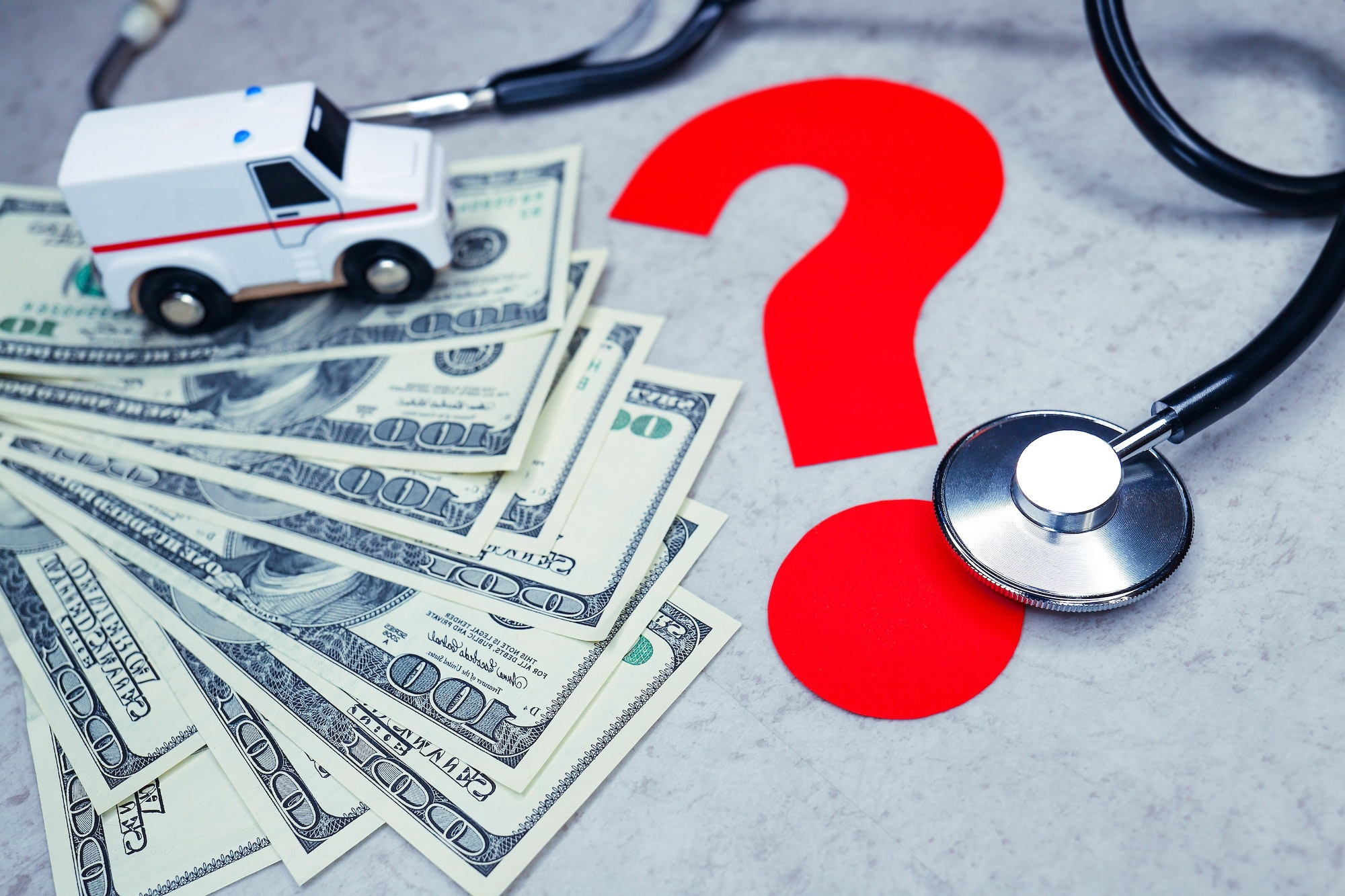 $100 bills, stethoscope, rescue squad or ambulance and red question mark
