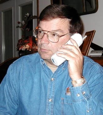 Bruce Suenram in denim shirt talking on a cordless telephone