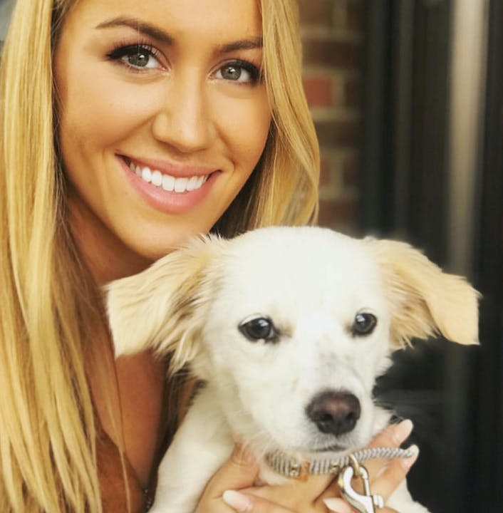 Young Caucasian woman holding up her dog