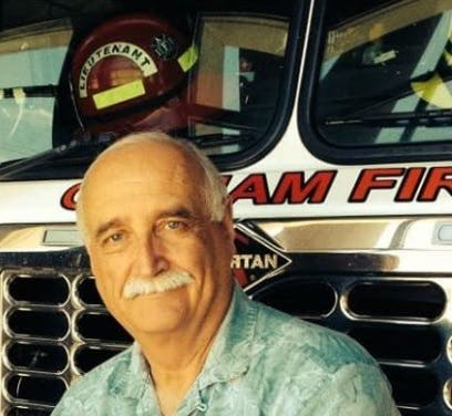 Bob Skaggs in print shirt in front of a fire truck
