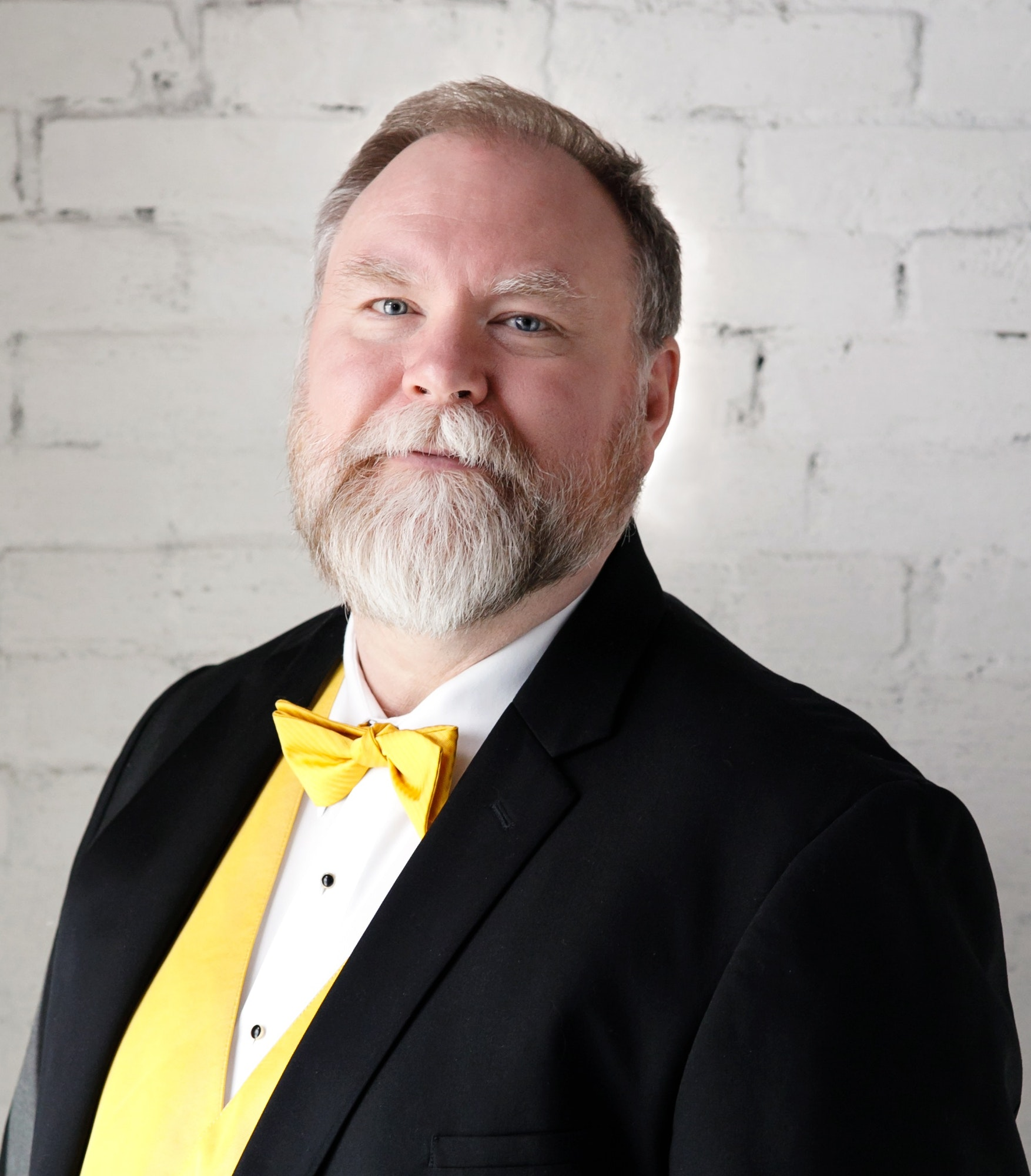 Monte Olsen in a tuxedo with yellow cummerbund and bow tie