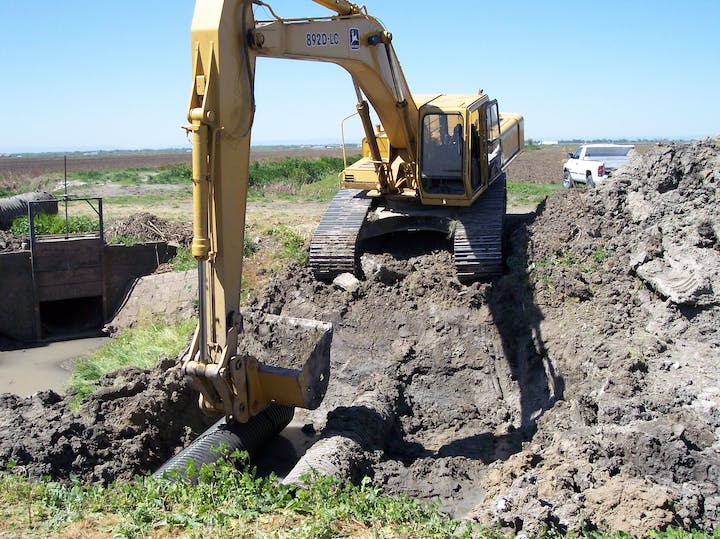 heavy equipment repairing a damaged levee