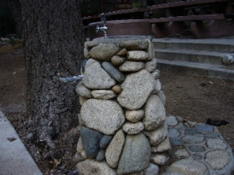 Dunsmuir Park in picnic area is a rock lined drinking fountain. Picnic tables in background.