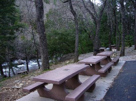 A line of cast cement picnic tables.