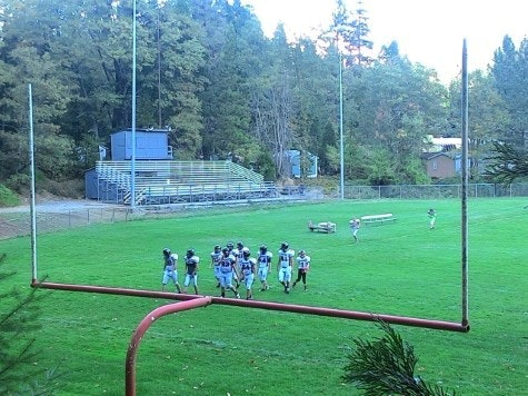 Looking over goalpost at Dunsmuir High School football team, grass, new grandstand and trees in background.